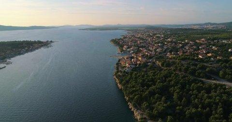 Aerial, tracking, drone shot, of the Brodarica village, on the mediterranean, croatian shore and the adriatic sea, near Sibenik, on a sunny, summer evening, in Croatia