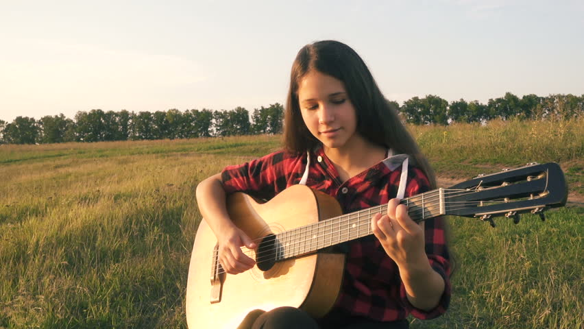 Young girl playing guitar on the green meadow at sunset, slow motion, part 1 | Shutterstock HD Video #1027792595