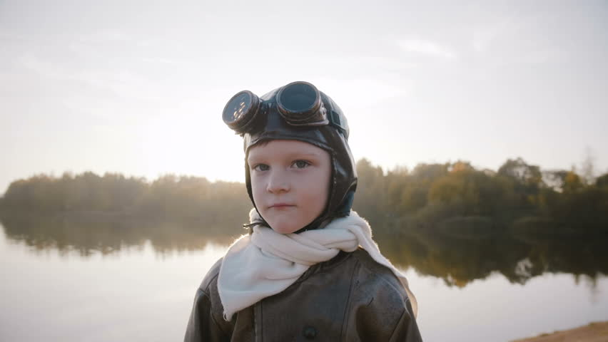 Portrait of serious little boy looking at camera in retro pilot glasses near sunset lake with backlight slow motion. | Shutterstock HD Video #1027831985
