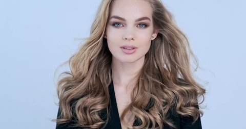 Beautiful young blonde woman with  long hair. Fashion model looks to the camera. Stunning face of a caucasian girl. Sexy model with a beautiful blue eyes. Slow motion. Beauty concept. 4k footage.