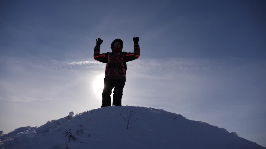 Traveler rejoices in his victory at the top of a snowy hill, jumps and waves his arms, a happy man. tourist comes down from the mountains lit by the sun. Slow motion | Shutterstock HD Video #1027889435