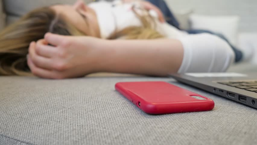 A young girl lies on the sofa and takes the phone.   Shutterstock HD Video #1027931315