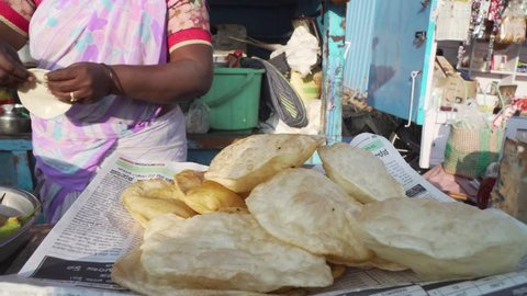 Panning shot across female frying breads in oil pan. Street food market trader in Hampi, India.