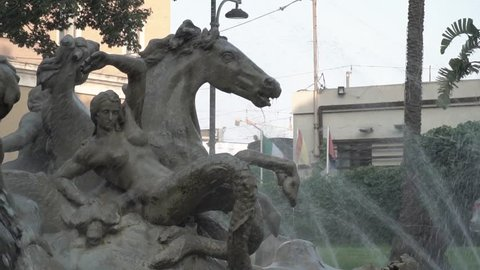Slow motion water jets spraying onto a concrete sculpture at Fontana di Proserpina in Catania, Italy