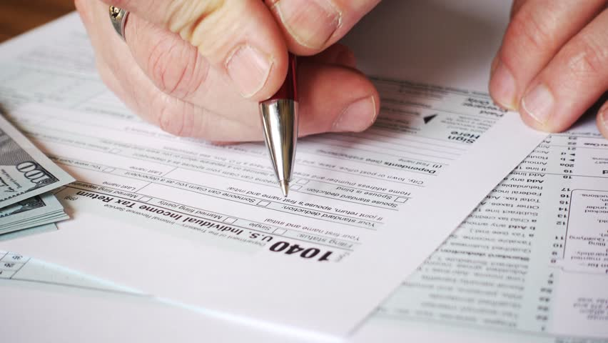 Man filling US tax form. tax form us business income office hand fill concept | Shutterstock HD Video #1028013455