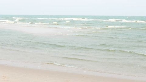 Many waves gently washing ashore on a peaceful inviting tropical beach.