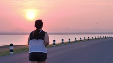 Overweight Asian women jogging in the street in the early morning sunlight. concept of losing weight with exercise for health. Slow motion, Rear View