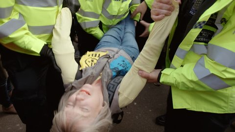LONDON, circa 2019 - Close-up shot of a female Extinction Rebellion demonstrator taken away by police officers after being arrested in Oxford Circus, London, UK