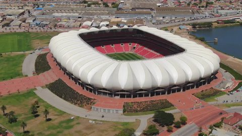 Port Elizabeth, South Africa - circa 2010s: Close up aerial orbit of Nelson Mandela Bay Stadium, looking through the roof, seeing goal posts on soccer field on a sunny summer day
