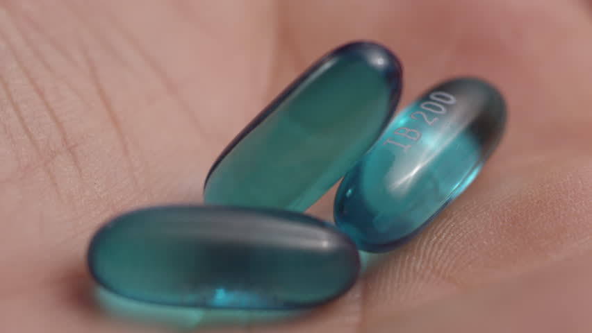 Macro close-up of a pile of blue ibuprofen liquid gel pills dropping into a human hand | Shutterstock HD Video #1028119505