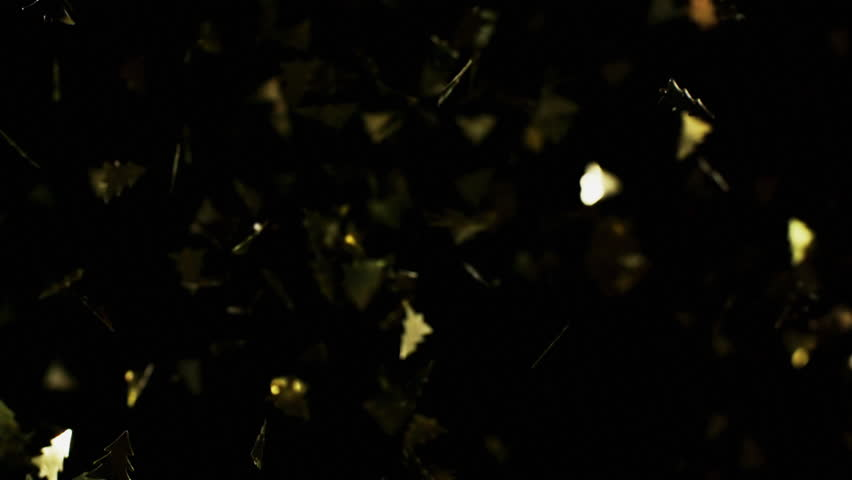 Golden christmas tree particles flying after being exploded, bright confetti bouncing against camera flying and falling down on black background. Top view close up slow motion | Shutterstock HD Video #1028119565