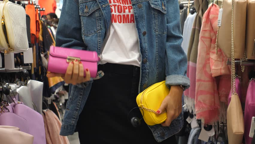 Fashionable Girl Shopping For Colorful Bags In Store. | Shutterstock HD Video #1028136335