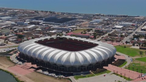 Port Elizabeth, South Africa - circa 2010s: Aerial fly forward, tilt down onto Nelson Mandela Bay Stadium near ocean and lake. See unmaintained green soccer pitch between red seats and open white roof