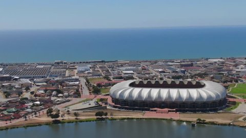 Port Elizabeth, South Africa - circa 2010s: Nelson Mandela Bay Stadium. Wide aerial view, turning around stadium that lies between a lake and the ocean. Large container ships out at sea