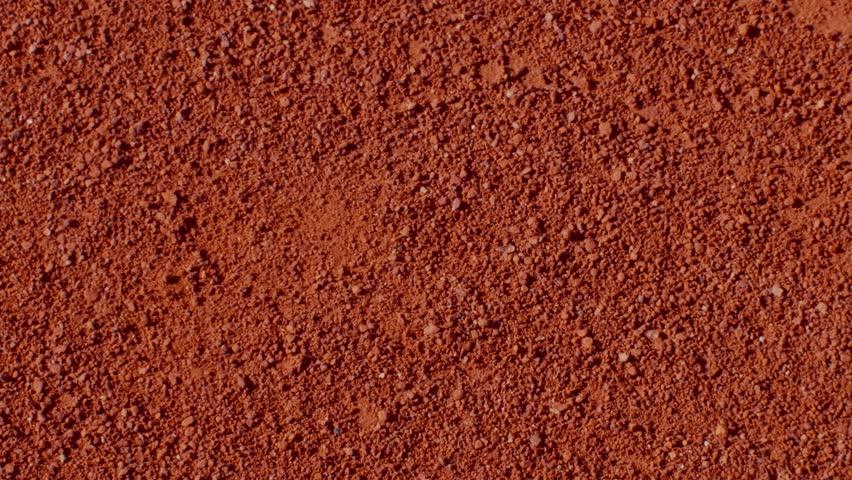 Tennis player bouncing tennis ball on a red tennis court before serving. 180fps   Shutterstock HD Video #1028177855