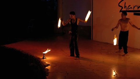 EGYPT, SHARM EL SHEIKH, APRIL 8, 2019: Fire Show Performance on Stage. Beautiful young man sexually dancing with fiery fans on a night show. Slow Motion. Boys performed fire dances in night. Hotel