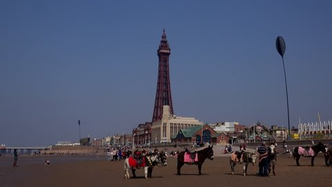 Blackpool, Lancashire / England - April 18 2019: Blackpool is famous for its tower which is a similar in design to the Eiffel tower in Paris. It is a holiday seaside resort in the UK time lapse 4K