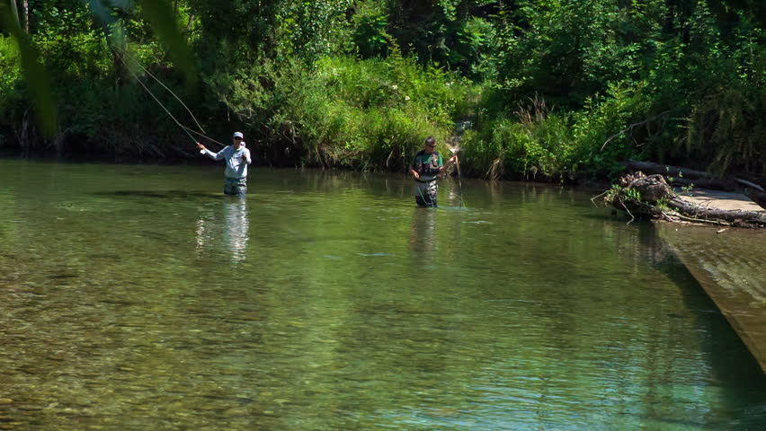 A man is throwing his fishing rod very far away. Two fishermen are spending their day fishing in the water of this river.