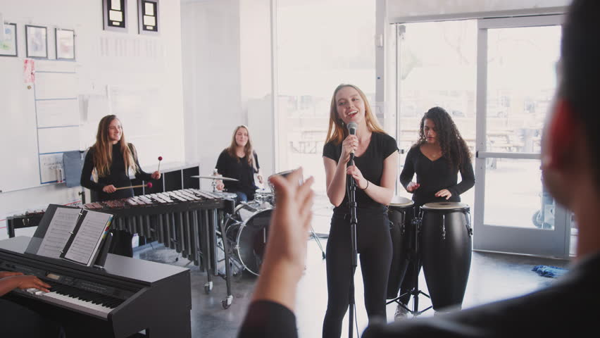 Teacher Watching Students At Performing Arts School Playing In Band At Rehearsal  | Shutterstock HD Video #1028225975
