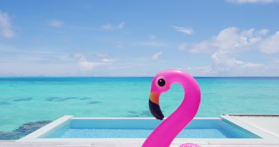 Funny vacation travel concept with inflatable pink flamingo float toy mattress in luxury swimming pool. Luxury lifestyle summer holidays travel background video. | Shutterstock HD Video #1028273585