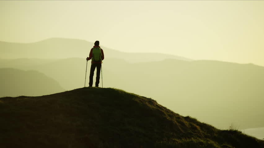 Silhouette of fitness Caucasian European female hiker with Nordic sticks and rucksack enjoying trekking Snowdonia National Park Wales RED MONSTRO #1028325695