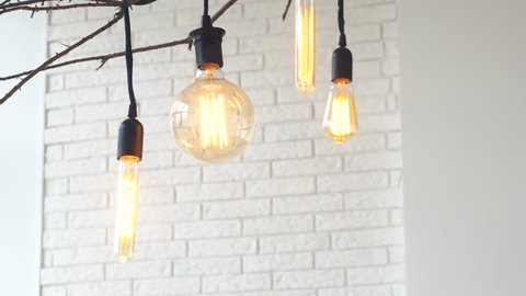 Close-up of man's palm touching large electric lamp bulb in light room against white brick wall. Media. Electricity concepts