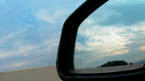 View in rear mirror from car on highway, personal transportation, car driving on motorway along concrete wall