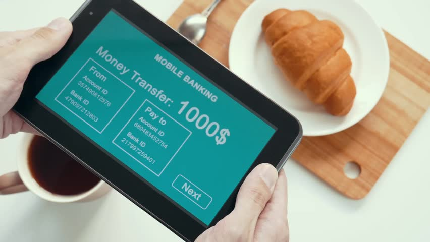 A successful person makes a money transfer through a mobile bank, having breakfast with a croissant and coffee. Blue custom interface design. The interface is not real. Information fictional. | Shutterstock HD Video #1028362775