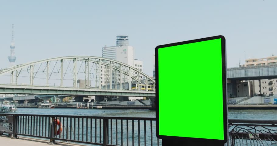 Modern billboard with a green screen, on the bank of the river in Tokyo, boat and subway train passes | Shutterstock HD Video #1028365865