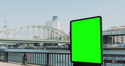 Modern billboard with a green screen, on the bank of the river in Tokyo, boat and subway train passes
