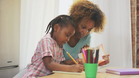 Afro-American mother and little daughter doing homework writing and reading at home