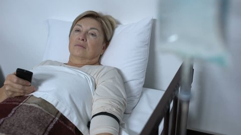 Weak aged woman patient watching TV at hospital ward, falling asleep in sickbed