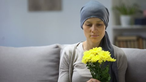 Recovery after cancer, woman in headscarf smelling flowers and enjoying life