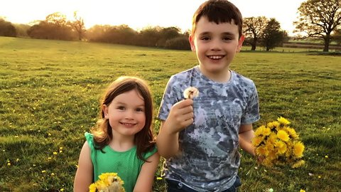 Young children running and laughing towards the camera holding dandelions in a spring field