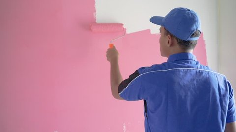 worker with blue uniform painting on the wall room with pink color