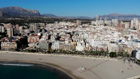 Aerial footage of the Spanish town of Benidorm in Alicante, showing the high-rise hotels and apartments and the beautiful sandy north side beach taken on a sunny day at the old town area of Benidorm