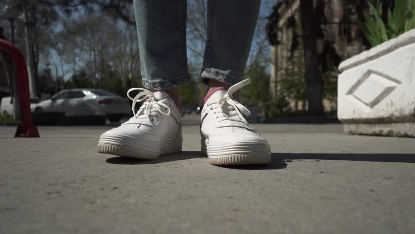 A woman's legs wearing white simple sneakers and jeans coming in and out of the scene. Walking urban lifestyle concept.      Shutterstock HD Video #1028544965