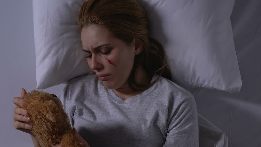 Lady with wounded face hugging teddy bear, crying in bed, victim needs support #1028591735