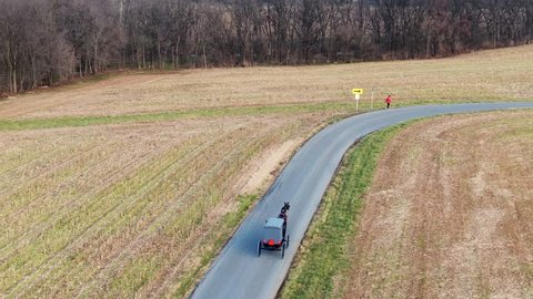 Aerial Amish horse and buggy traveling down the road being passed by a motorcycle then passing a man out for a walk along the roadside, Lancaster County, PA. Concept: traditional vs modern
