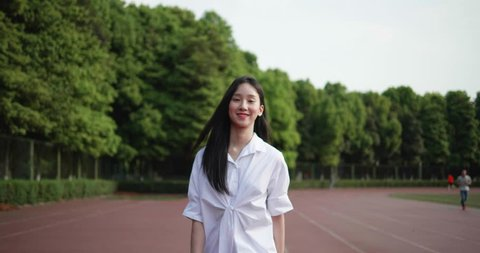 Beautiful young Chinese girl student walking in the playground. Spring day,long-haired Asian girl in a white shirt smiles at the camera as she walks. Sweet-looking girl turns a circle at the camera.