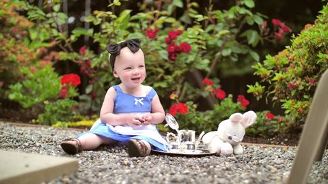 Baby dressed as alice in wonderland has a tea party