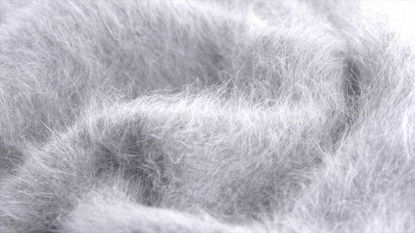 Mohair Wool background. Alpaca wool mohair clothes texture closeup. Cashmere Soft and fluffy grey merino wool macro shot. Woolen fabric. Knitted texture surface Rotated. Slow motion. 4K UHD video