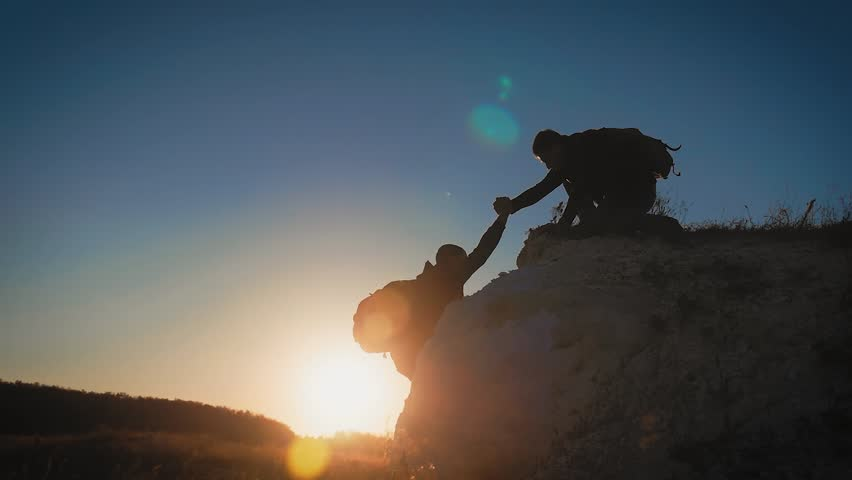 Silhouette of helping hand between two climber. two hikers on top of the mountain, a man helps a man to climb a sheer stone. couple hiking help each other silhouette in mountains with sunlight. | Shutterstock HD Video #1028667455