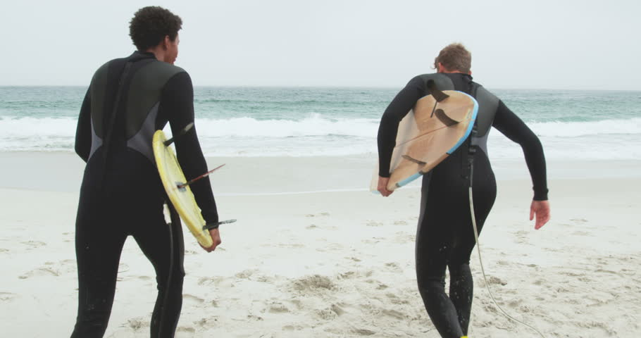 Rear view of two male surfers running together with surfboard on the beach. They are interacting with each other
