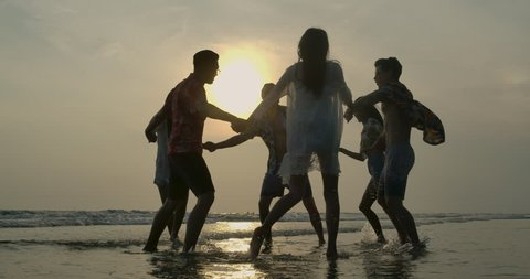 Group of happy friends guys and girls playing in water at beach party on sunset. People with travel, holiday and party concept. Slow motion.