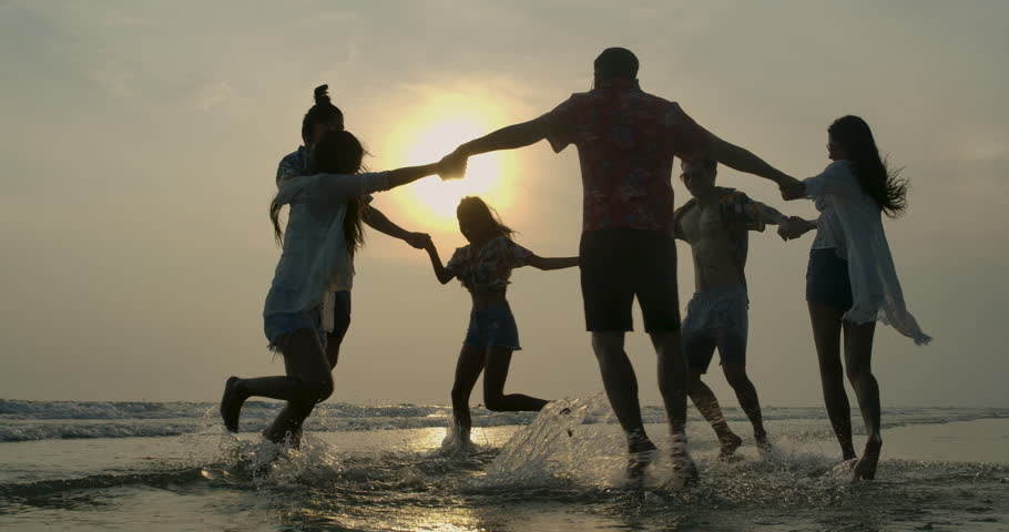 Group of happy friends guys and girls playing in water at beach party on sunset. People with travel, holiday and party concept. Slow motion. | Shutterstock HD Video #1028688395