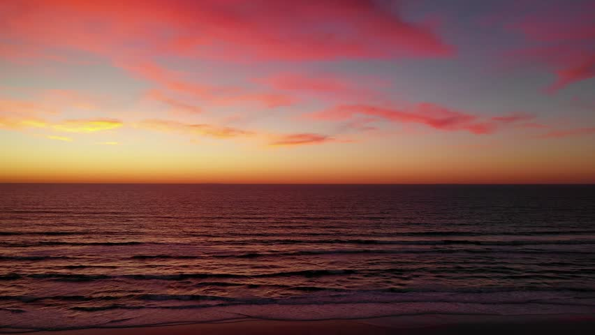 Aerial drone view over the ocean at sunset with neon pink clouds across the dreamy sky. #1028706875
