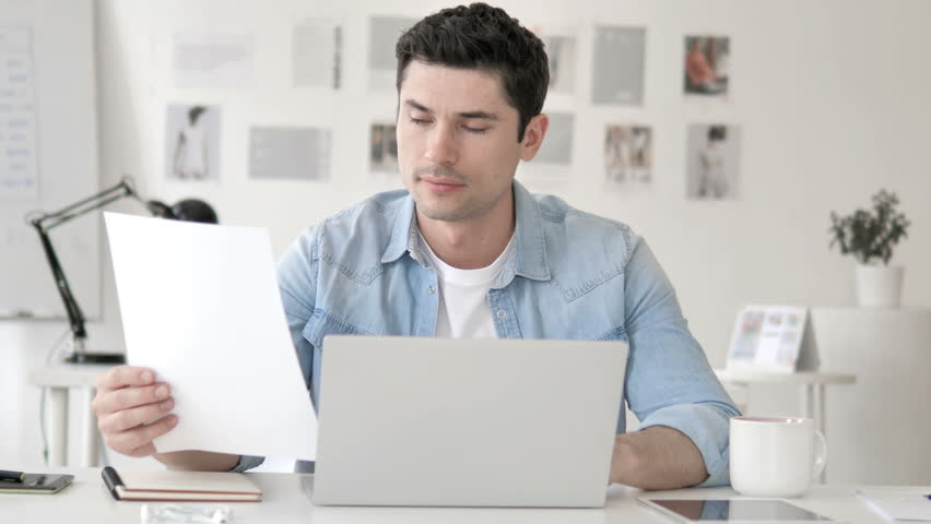 Casual Young Man Working in Office on Contract, Paperwork | Shutterstock HD Video #1028740115