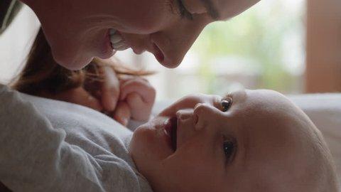 close up mother kissing happy baby laughing enjoying loving mom nurturing toddler at home