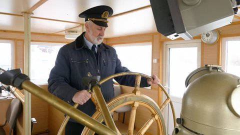 Elderly grey-haired captain of the ship in peaked cap at the helm in the wheelhouse is talking about his job. Captain at the steering wheel of the ship